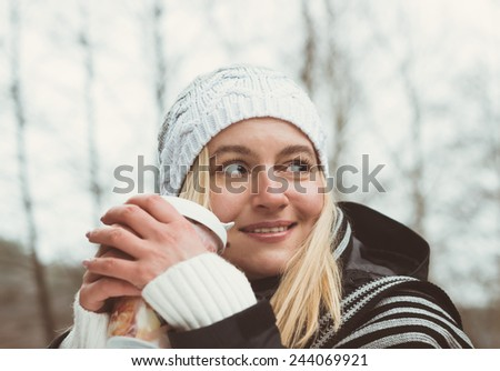 Smiling fashionable blonde drinking coffee outdoors. Toned - stock photo