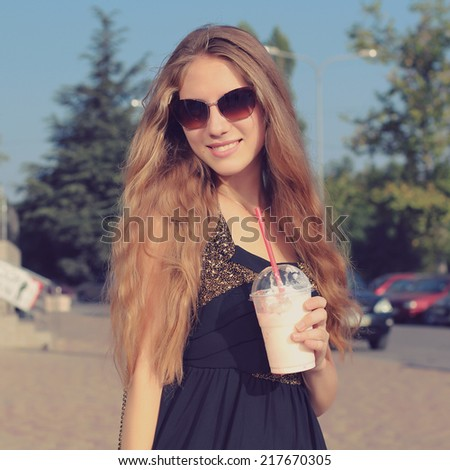 Smiling fashionable blonde drinking drinking a strawberry milkshake outdoors. Photo toned style Instagram filters - stock photo