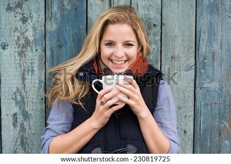 Smiling fashionable blonde drinking hot beverage - stock photo