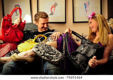 Smiling fashionable rich attractive couple sitting on sofa at home laying under lots of handbags - stock photo