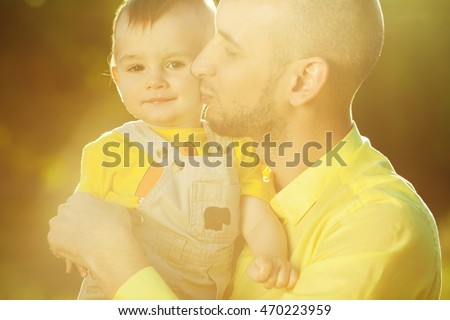 Smiling father and annoyed little son walking together in a park. Dad holding baby. Sunny summer day. Close up. Outdoor shot
