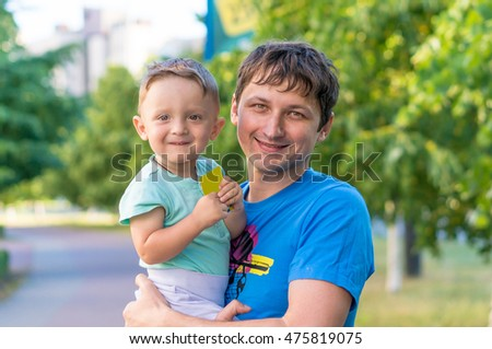 Smiling father and baby boy son having fun at the park. Funny cute child making vacations and enjoying summer. Happy family. Positive human emotions, feelings, joy.