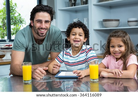 Smiling father and children using tablet in kitchen - stock photo