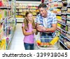 Smiling father and daughter at the supermarket using smartphone - stock photo