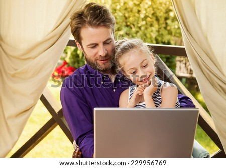 Smiling father and daughter looking at laptop computer during sunny summer day. Happy family time outdoor on garden terrace - modern lifestyle or holiday concept. - stock photo
