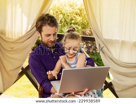 Smiling father and daughter playing game on laptop computer during sunny summer day. Happy family time  outdoor on garden terrace - modern lifestyle or holiday concept. - stock photo
