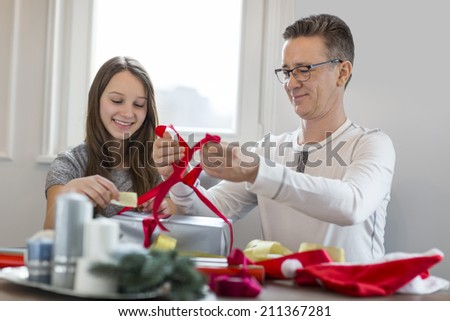 Smiling father and daughter wrapping Christmas present at home - stock photo
