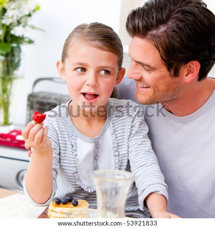 Smiling father and his daughter having breakfast together in the kitchen - stock photo