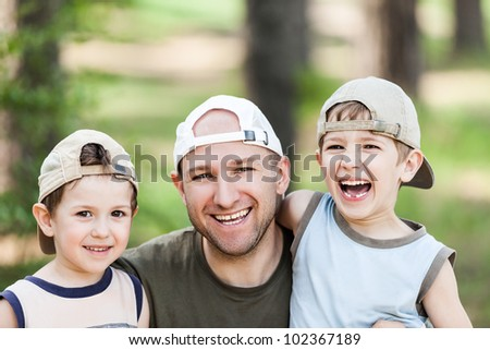 Smiling father and little sons - family happiness