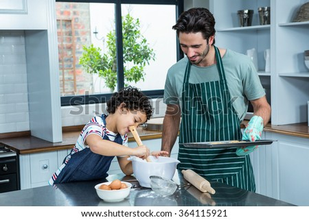 Smiling father and son cooking biscuits in the kitchen at home - stock photo