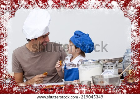 Smiling father and son eating homemade cookies against snow