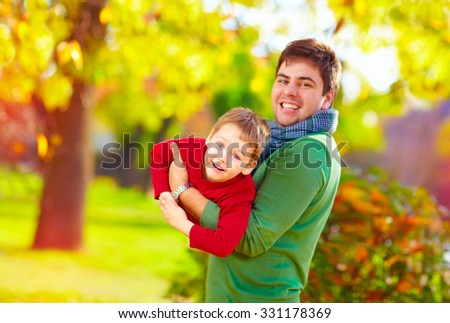 smiling father and son having fun in autumn park