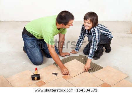 Smiling father and son laying ceramic floor tiles together - stock photo