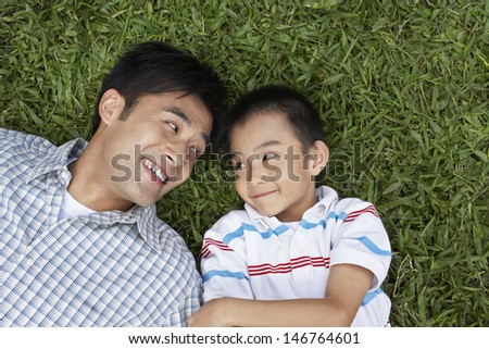 Smiling father and son looking at each other while lying on grass at park - stock photo