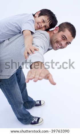 Smiling father and son playing together with their backs - stock photo