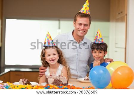 Smiling father celebrating birthday with his kids - stock photo
