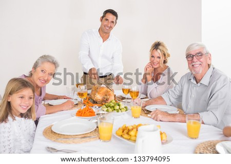 Smiling father cutting slices of turkey for family dinner - stock photo