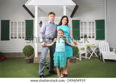 Smiling father, mother and daughter stand near porch of their new house. - stock photo
