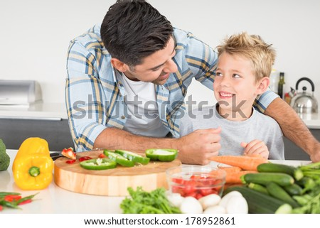 Smiling father preparing vegetables with his son at home in kitchen - stock photo