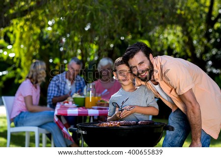 Smiling father with son by barbecue grill against family in yard - stock photo