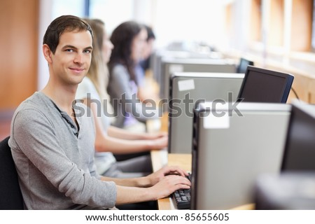Smiling fellow students in an IT room with the camera focus on the foreground - stock photo