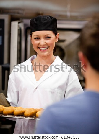Smiling female baker holding baguettes ready to serve her customer in a bakery - stock photo