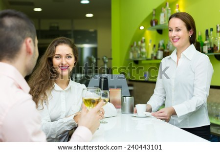 Smiling female barista and two young clients in small bar. Focus on girl - stock photo