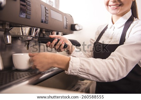 Smiling female barista is preparing espresso at coffee shop. - stock photo