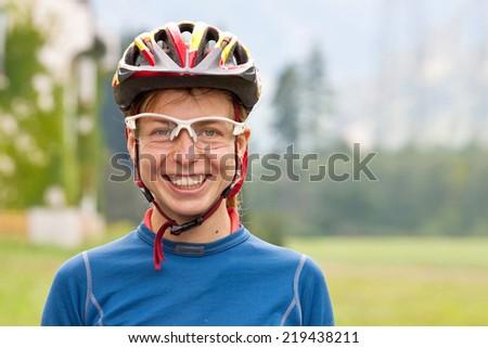 Smiling female biker with helmet outdoor - stock photo