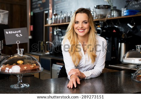 Smiling female cafe owner standing behind the bar - stock photo