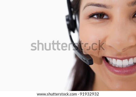 Smiling female call center agent with headset against a white background