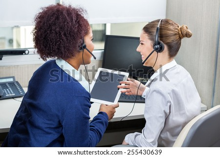 Smiling female call center employees discussing while using digital tablet in office - stock photo