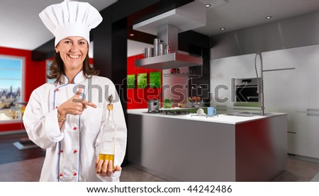 Smiling female chef in a modern kitchen with a bottle of olive oil