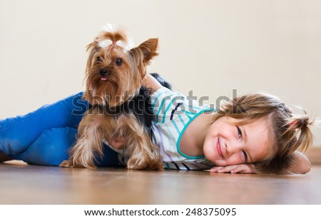 Smiling female child embraces and playing with charming Yorkie at home