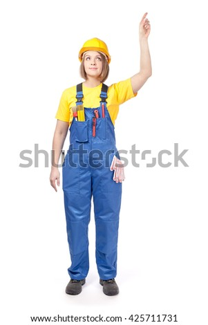 smiling female construction worker or decorator in yellow hardhat and workwear pointing up isolated on white background