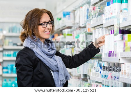 Smiling female consumer choosing product in pharmacy - stock photo