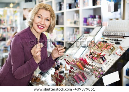 Smiling female customer buying red lipstick in makeup section