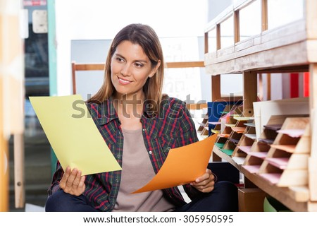 Smiling female customer choosing between yellow and orange papers in shop