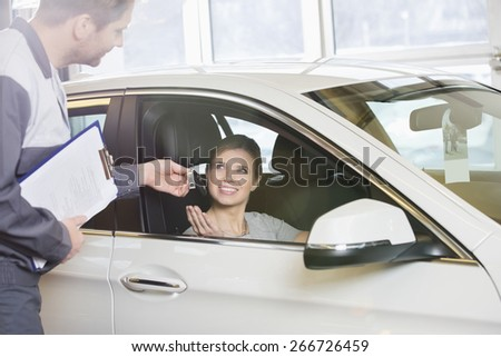 Smiling female customer receiving car key from mechanic in workshop - stock photo
