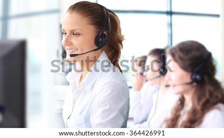 Smiling female customer service representative talking on headset with colleagues in background at office
