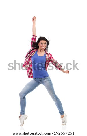 Smiling female dancer posing and punching the air. Full length studio shot isolated on white.