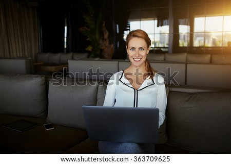 Smiling female designer using laptop computer for creates opening inauguration for new restaurant, cheerful woman looking at camera while sitting with portable net-book in modern coffee shop interior  - stock photo