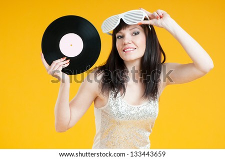 Smiling female DJ posing with a vinyl record over yellow background, horizontal shot - stock photo