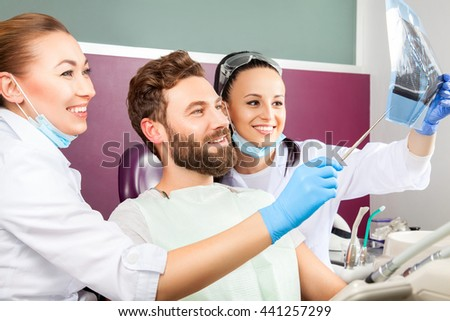 Smiling female doctor and her assistant showing teeth x-ray to male patient in dental hospital. Handsome men with beard sitting in medical chair and looking at the picture.