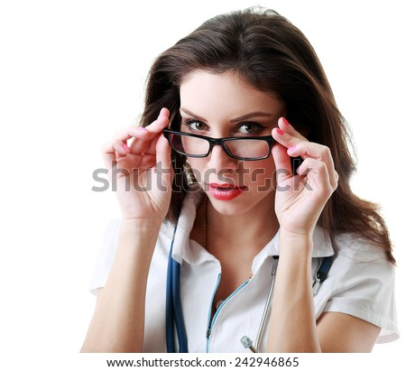 Smiling female doctor looking at camera over the glasses. - stock photo