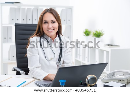 Smiling female doctor sitting at computer. Office at background. Concept of work. - stock photo