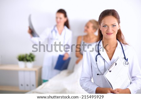 Smiling female doctor with a folder in uniform standing at hospital - stock photo