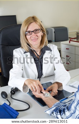 Smiling Female Doctor With Accessories For Measuring Blood Pressure - stock photo