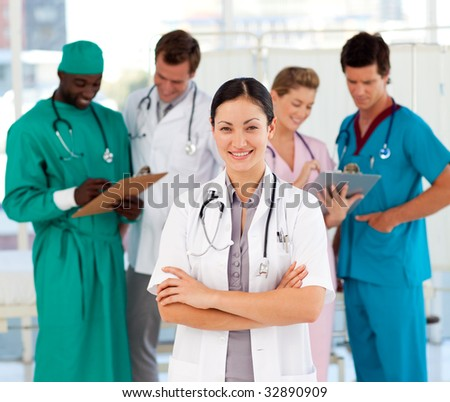 Smiling female doctor with her team in the background