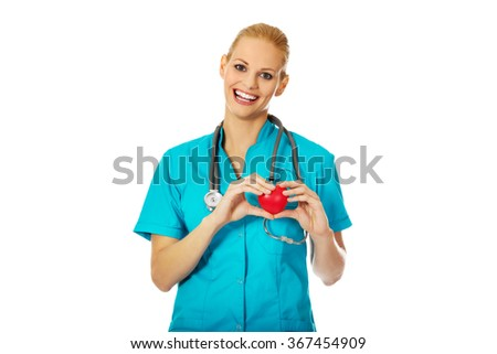Smiling female doctor with stethoscope holding heart model